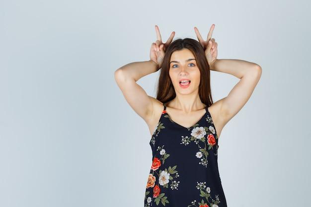Mooie jonge vrouw bunny oren gebaar in blouse tonen en geamuseerd kijken