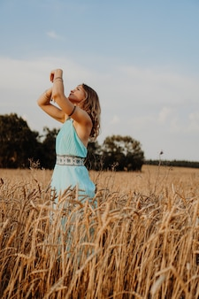 Mooie jonge vrouw dansen in het veld bij zonsondergang