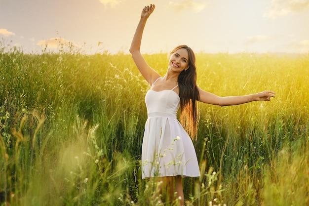 Mooie jonge vrouw dansen in het veld over de zonsondergang