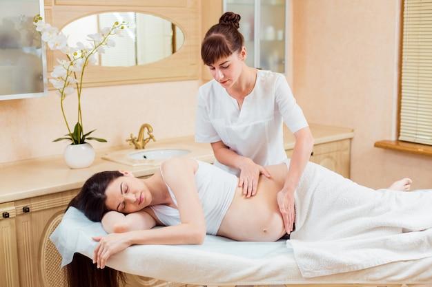 Mooie jonge vrouw de massagetherapeut van de artsenarts in een de kosmetiekruimte die een massage doen aan een zwanger meisje met lang haar