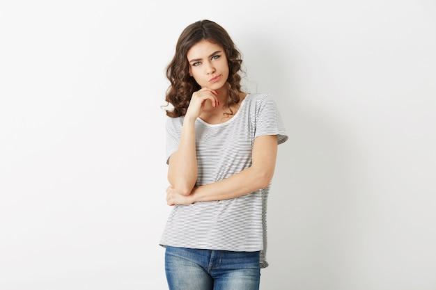 Mooie jonge vrouw, denken over probleem, hipster stijl, gekleed in spijkerbroek, t-shirt, geïsoleerd op een witte achtergrond