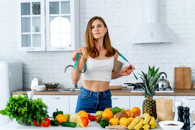 Mooie jonge vrouw dichtbij in de keuken met gezond voedsel.