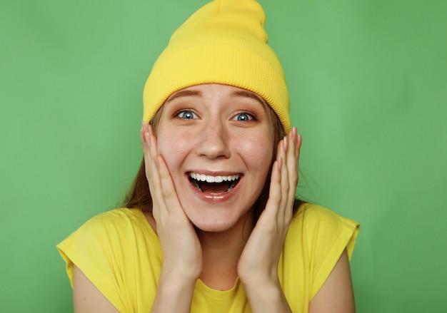 Mooie jonge vrouw die aan camera over groen glimlacht