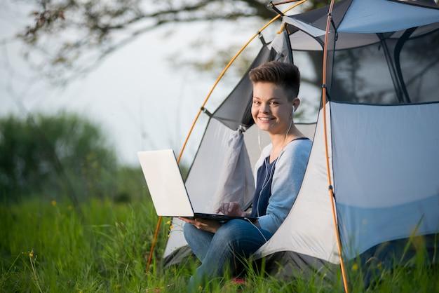 Mooie jonge vrouw die aan de camera glimlachen die vreugdevol in een tent zitten terwijl het kamperen gebruikend haar laptop