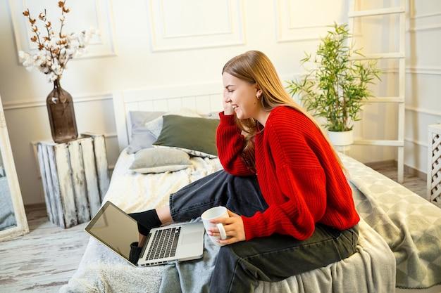 Mooie jonge vrouw die aan een laptop werkt die thuis op het bed zit, ze drinkt koffie en glimlacht. thuiswerken tijdens quarantaine. meisje in trui en spijkerbroek thuis op bed