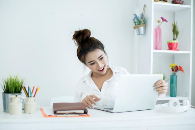 Mooie jonge vrouw die aan haar laptop in haar ruimte werkt.