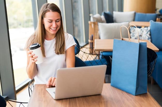 Mooie jonge vrouw die aan laptop werkt