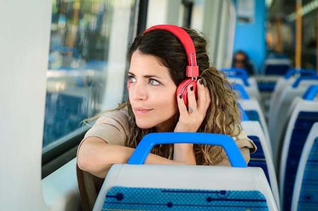 Mooie jonge vrouw die aan muziek in een trein luistert.