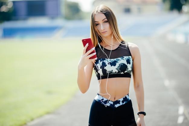 Mooie jonge vrouw die aan muziek in het stadion luistert