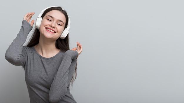Mooie jonge vrouw die aan muziek luistert