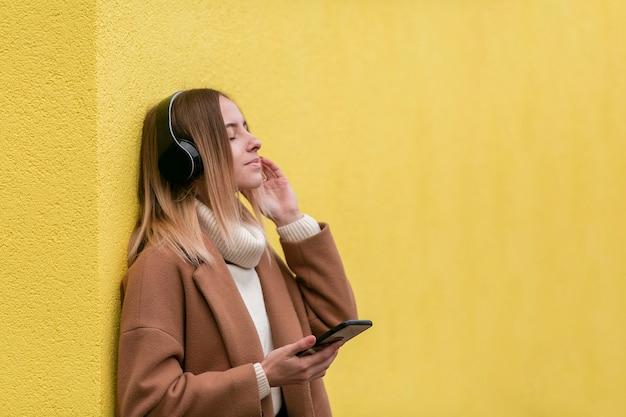 Mooie jonge vrouw die aan muziek op hoofdtelefoons met exemplaarruimte luistert