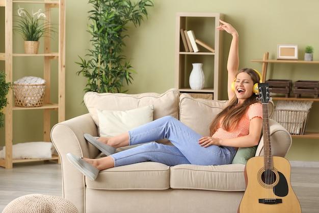 Mooie jonge vrouw die aan muziek thuis luistert