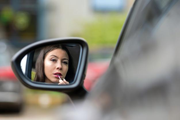 Mooie jonge vrouw die achteruitkijkspiegel bekijkt die lippenstift toepast