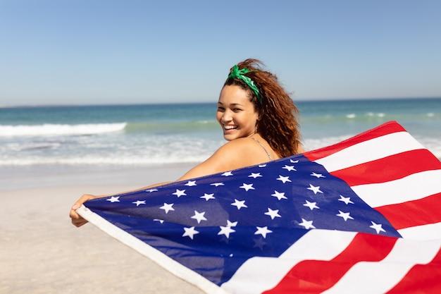 Mooie jonge vrouw die amerikaanse vlag op strand in de zonneschijn golft