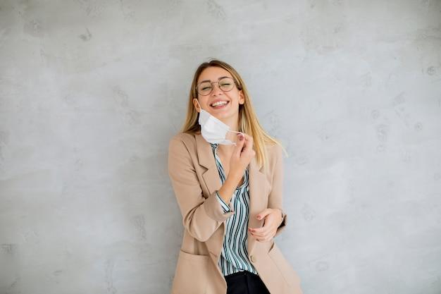 Mooie jonge vrouw die bij de grijze muur staat en een ademhalingsmasker opstijgt van de coronavirusziekte