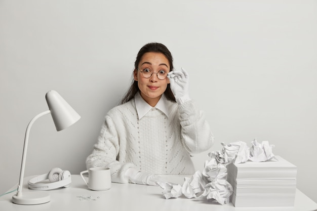 Mooie jonge vrouw die bij haar bureau bestudeert