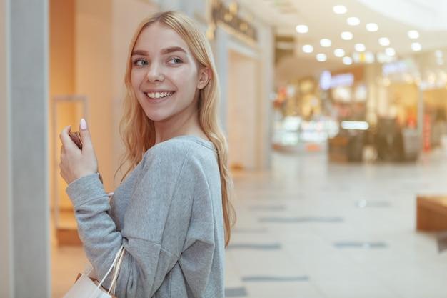 Mooie jonge vrouw die bij het lokale wandelgalerij winkelt
