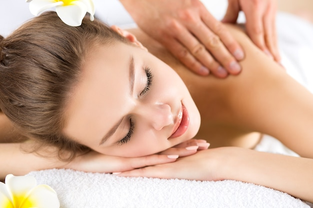 Mooie jonge vrouw die bij kuuroordsalon ligt. huid- en lichaamsverzorging, ontspanning, massage en cosmetologieconcept