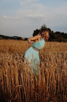 Mooie jonge vrouw die bij zonsondergang in het veld danst