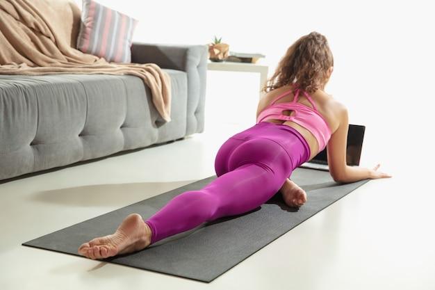 Mooie jonge vrouw die binnenshuis traint, yogaoefening doet op grijze mat thuis