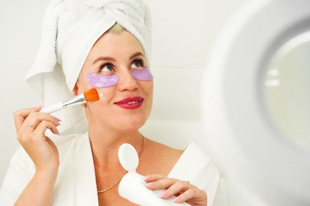 Mooie jonge vrouw die biologische cosmetica op haar huid aanbrengt