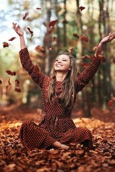 Mooie jonge vrouw die bladeren gooit in het herfstbos
