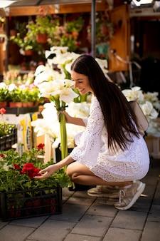 Mooie jonge vrouw die bloemen koopt op de bloemenmarkt