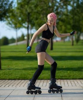 Mooie jonge vrouw die buiten rolschaatst