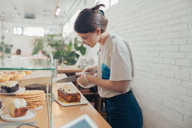 Mooie jonge vrouw die cake snijdt in de bakkerij