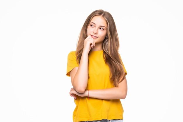 Mooie jonge vrouw die camera op witte muur bekijkt