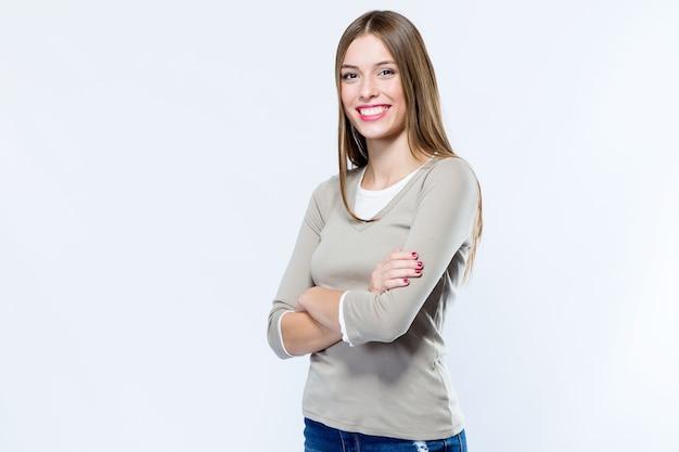 Mooie jonge vrouw die camera over witte achtergrond bekijkt.