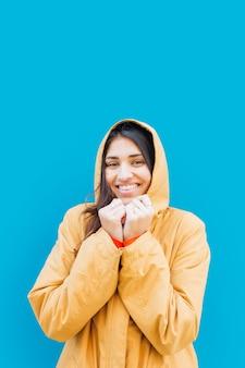 Mooie jonge vrouw die camera vooraan blauwe achtergrond bekijkt
