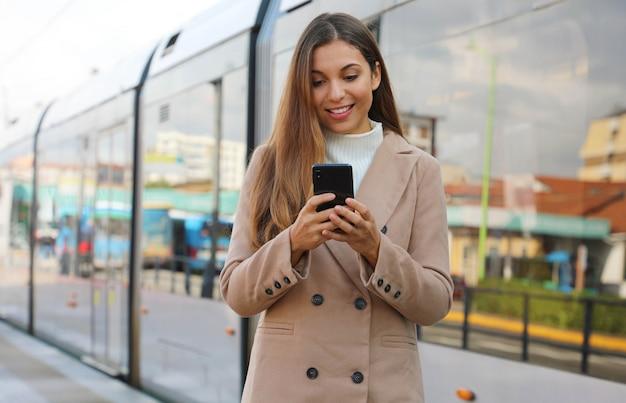 Mooie jonge vrouw die cellulaire het bijwerken van informatie over stadsvervoer online houdt. glimlachende zakenvrouw tevreden met online ticketservice betalen voor elektrisch vervoer via smartphone.
