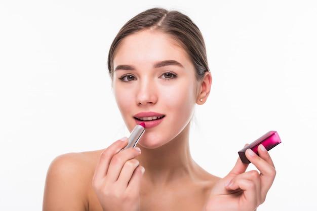 Mooie jonge vrouw die chapstick toepast op lippen die over witte muur worden geïsoleerd.