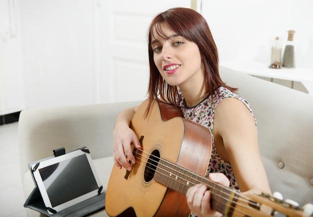 Mooie jonge vrouw die de akoestische gitaar speelt