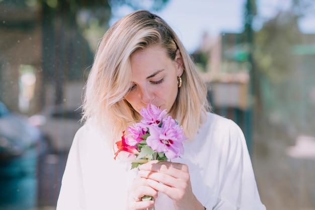 Mooie jonge vrouw die de bloemen ruikt