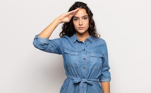 Mooie jonge vrouw die de camera begroet met een militaire groet in een daad van eer en patriottisme, respect tonen