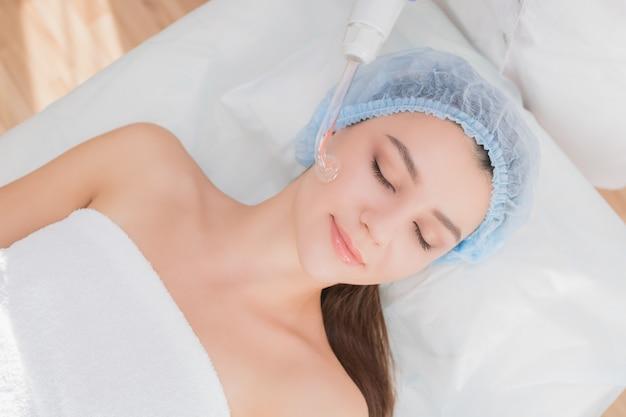 Mooie jonge vrouw die de elektrische massage van de darsonvalprocedure ontvangt bij schoonheidssalon.