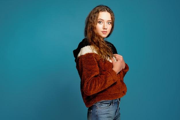 Mooie jonge vrouw die de herfst rode laag draagt