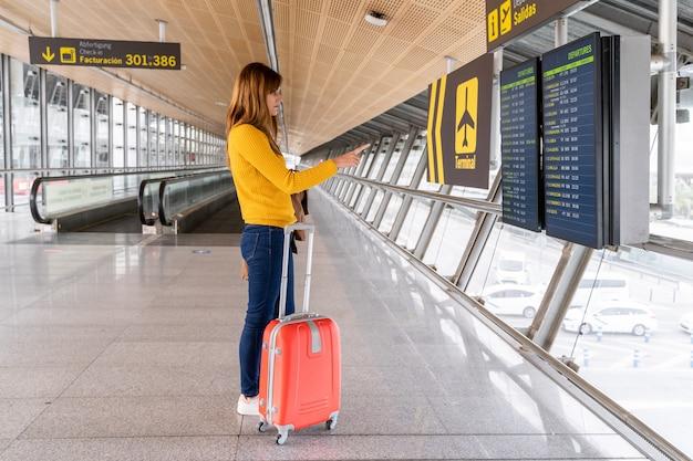 Mooie jonge vrouw die de vertrektijd van haar vlucht controleren op de informatieborden op de luchthaven met haar bagage