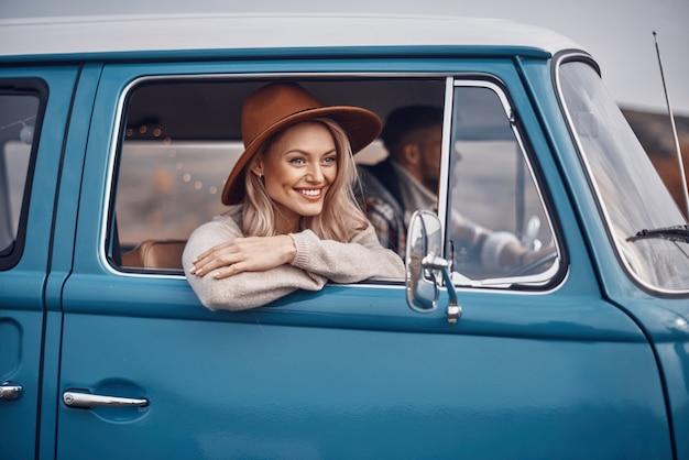 Mooie jonge vrouw die door een raam kijkt en glimlacht terwijl haar vriendje auto rijdt