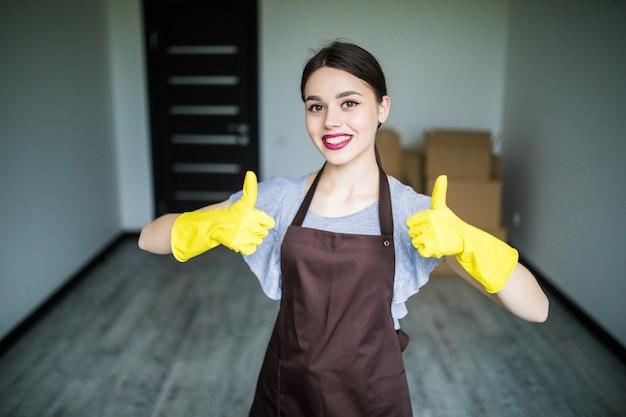 Mooie jonge vrouw die duim toont en schoonmaakspullen voor raam vasthoudt