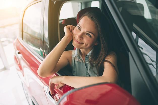 Mooie jonge vrouw die een auto kopen bij dealership. vrouwelijke model zitten zit in het auto-interieur