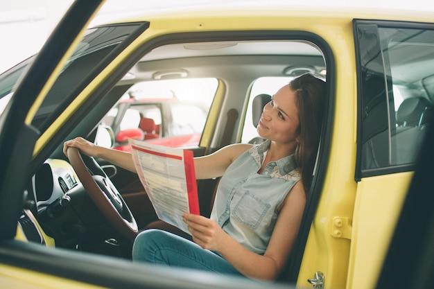 Mooie jonge vrouw die een auto kopen bij dealership.