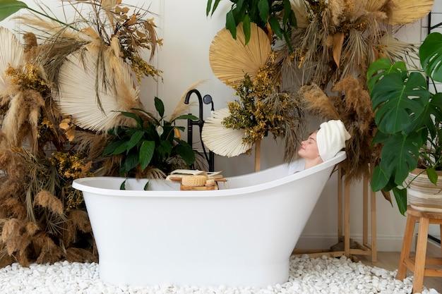 Mooie jonge vrouw die een bad neemt