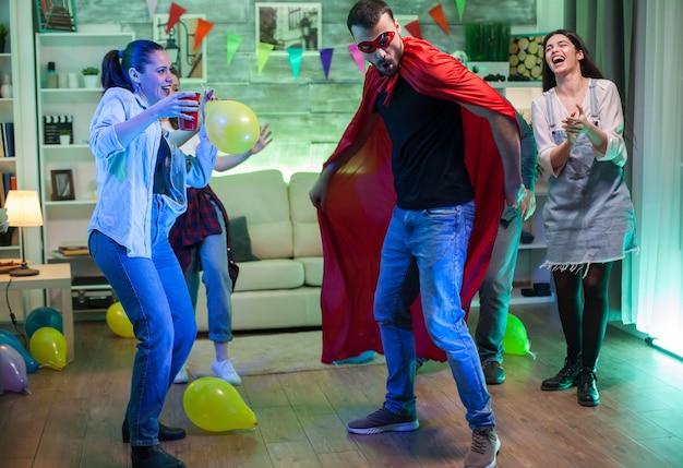 Mooie jonge vrouw die een ballon vasthoudt op een feestje en naar haar vriend kijkt, verkleed als een superheld.