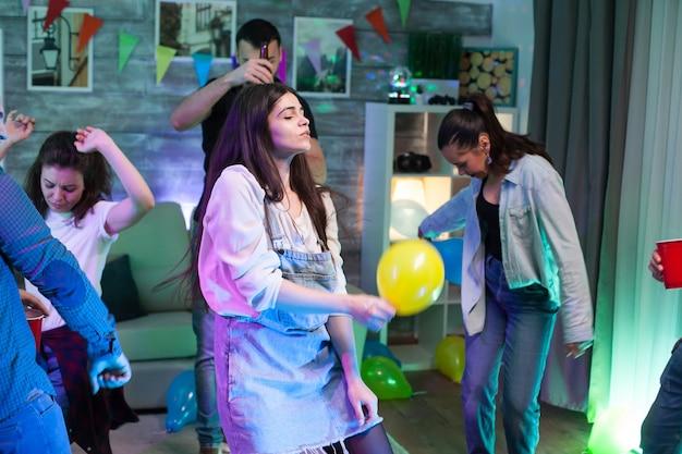 Mooie jonge vrouw die een ballon vasthoudt terwijl ze danst op een feestje met haar vrienden.