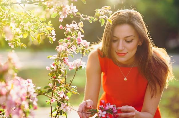 Mooie jonge vrouw die een bloem in het de lentepark ruikt
