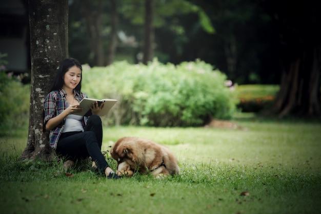Mooie jonge vrouw die een boek met haar kleine hond in een park in openlucht leest. levensstijl portret.