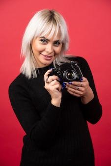 Mooie jonge vrouw die een camera houdt terwijl hij tegen rode achtergrond staat. hoge kwaliteit foto